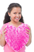 Little girl holding cushion in the shape of a heart — Stock Photo