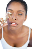 Concentrated woman using curler for her eyelash — Stock Photo