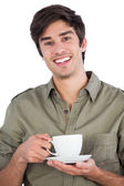 Smiling man holding cup of coffee — Stock Photo