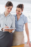 Businesswoman watching her co worker write on clipboard — Stock Photo