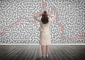 Puzzled businesswoman looking at a maze — Stok fotoğraf