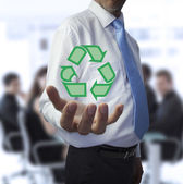 Businessman holding the recycling symbol — Stock Photo