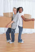 Smiling friends standing back to back holding moving boxes — Stock Photo