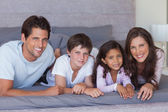 Cheerful family lying on bed — Stock Photo