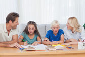 Parents helping their children doing their homework — Stockfoto