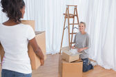 Young friends unpacking in their new home — Stock Photo