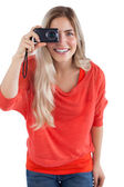 Blonde woman holding digital camera — Stock Photo