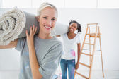 Happy housemates carrying rolled up rug in new home — Stock Photo