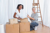 Happy friends unpacking boxes in new home — Stock Photo