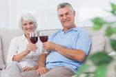Couple clinking their red wine glasses — Stock Photo