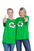 Two women wearing green recycling tshirts giving thumbs up — Stock Photo