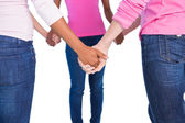 Women wearing pink for breast cancer holding hands — Stock Photo