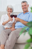 Husband and wife clinking their glasses of red wine — Stock Photo