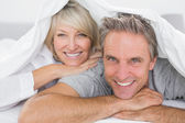 Couple smiling under the covers — Stockfoto