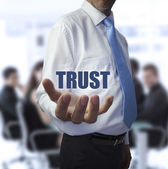 Smart businessman holding the word trust — Stock Photo