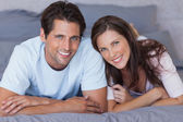 Delighted couple lying on bed — Stock Photo