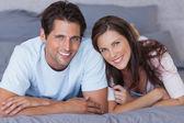 Radost pár ležící na posteli — Stock fotografie