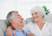 Pár směje a chatování na gauči — Stock fotografie