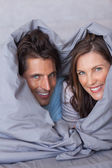Delighted couple having fun wrapped in their duvet — Stok fotoğraf