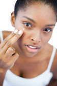 Pretty woman putting moisturizer on her face — Stock Photo