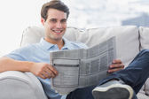 Man reading a newspaper sat on a couch — Stock Photo
