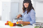 Pretty brunette chopping peppers — Stock Photo