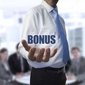 Elegant businessman holding the word bonus — Stock Photo