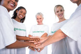 Group of female volunteers with hands together smiling at camera — Stock Photo