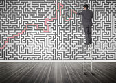 Businessman standing on a ladder solving maze puzzle — 图库照片