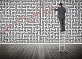 站在梯子上求解迷宫拼图上的商人 — 图库照片