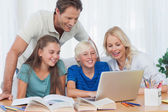 Parents and children using a computer — Stock Photo