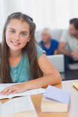 Cheerful girl doing her homework — Stock Photo