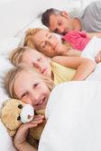 Jeune fille éveillée à côté de sa famille endormie — Photo
