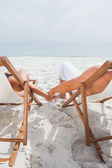 Cute couple lying on deck chairs — Stock Photo