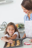 Little girl grabbing a cookie from a baking pan — Stock Photo