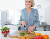 Happy woman chopping vegetables — Stock Photo