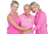 Happy women wearing pink tops and ribbons for breast cancer — Stock Photo