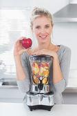 Hübsche frau, stützte sich auf ihre volle frucht entsafter und halten rot — Stockfoto