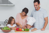Children looking at their mother who is cutting vegetables — Stock Photo