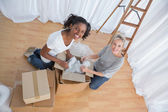 Pretty friends unpacking boxes in new home — Stock Photo