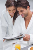 Lovely couple reading newspaper — Stock Photo