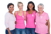 Smiling women wearing pink tops and breast cancer ribbons — Stock Photo