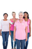 Supportive women wearing pink tops and breast cancer ribbons — Stock Photo