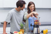 Couple putting fruits into blender — Stock Photo