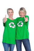 Two happy women wearing green recycling tshirts giving thumbs up — Stock Photo