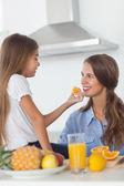 Menina jovem dando um segmento de laranja para a mãe dela — Foto Stock