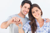 Man and wife holding a key with a house keychain — Stock Photo
