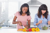 Cheerful friends preparing a salad together — Stock Photo