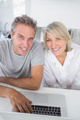 Smiling couple using their laptop in the morning looking at came — Stock Photo