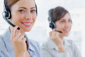 Smiling call centre agents with headsets at work — Stock Photo